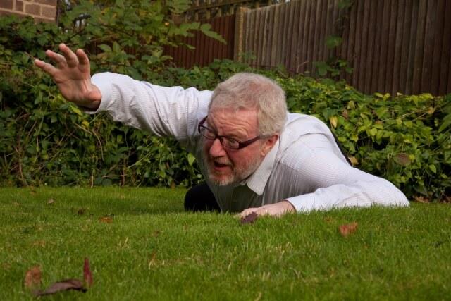 芝生で寝転がるおじさん